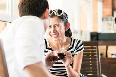 Asian couple in cafe flirting while drinking coffee Royalty Free Stock Photography