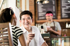 Asian couple in cafe flirting while drinking coffee stock photo