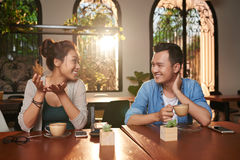 Asian Couple Chatting in Cafe. Portrait of cheerful Asian couple chatting in cafe and smiling while on date stock photos