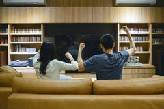 Asian couple cheering in front of TV in living room at night royalty free stock photography