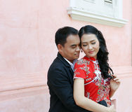 Asian couple in chinese style dress hold each other agianst pink wall Stock Photos