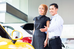 Asian couple choosing car in dealership stock photos