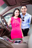 Asian couple choosing luxury car in dealership Royalty Free Stock Image