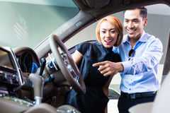 Asian couple choosing luxury car in dealership Royalty Free Stock Photos