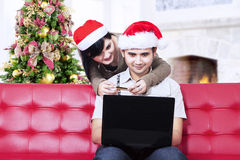 Asian couple in christmas hats shopping online. Young couple in Christmas hats shopping online at home Royalty Free Stock Image