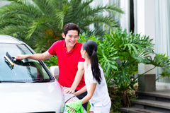Asian couple cleaning together car Stock Photography