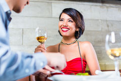 Asian couple clinking wine glasses in bar. Asian couple having dinner and drinking red wine in very fancy bar or restaurant Royalty Free Stock Images