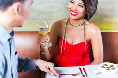 Asian couple clinking wine glasses in bar Royalty Free Stock Photo