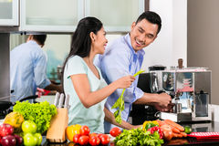 Asian couple cooking food together in kitchen. Asian couple, men and woman, cooking food together in kitchen and making coffee Royalty Free Stock Photography