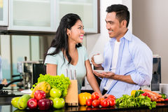 Asian couple cooking food together in kitchen. Asian couple, men and woman, cooking food together in kitchen and making coffee Stock Photography
