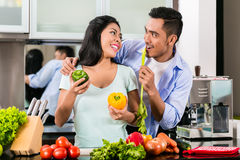 Asian couple cooking food together in kitchen Royalty Free Stock Photography