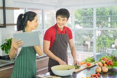 Asian couple are cooking in the kitchen. Man and Woman smiling looking menu from tablet. Man are cutting vegetables with knives. p stock images