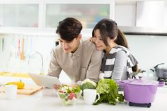 Asian couple cooking in kitchen. Young asian couple cooking in kitchen Stock Photography