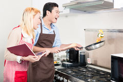 Asian couple cooking vegetables in frying pan Royalty Free Stock Image