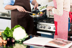 Asian couple cooking vegetables in frying pan Stock Image