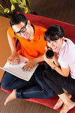 Asian couple on the couch with a laptop Royalty Free Stock Images