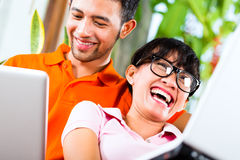 Asian couple on the couch with a laptop Stock Photography