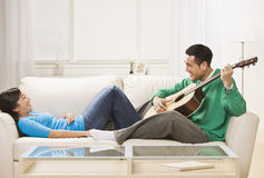 Asian couple on couch relaxing together. royalty free stock photo
