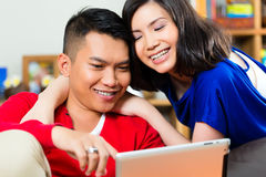 Asian couple on the couch with a tablet pc Royalty Free Stock Photography