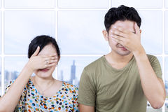 Asian couple cover faces in apartment Royalty Free Stock Images
