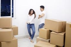 Asian couple dances near piles of cardboard boxes stock photos