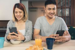 Asian couple distracted at table with newspaper and cell phone while eating breakfast. stock images