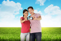 Asian couple doing selfie on meadow Stock Photo