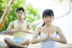 Asian couple doing yoga on the beach. Royalty Free Stock Photo