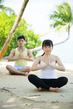 Asian couple doing yoga on the beach. Royalty Free Stock Images