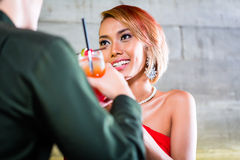 Asian couple drinking cocktails in bar. Asian couple drinking cocktails in fancy bar stock image