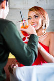 Asian couple drinking cocktails in bar. Asian couple drinking cocktails in fancy bar royalty free stock photos