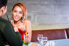 Asian couple drinking cocktails in bar. Asian couple drinking cocktails in fancy bar royalty free stock photography