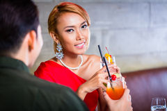 Asian couple drinking cocktails in fancy bar. Couple drinking cocktails in fancy bar Stock Photo