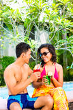 Asian couple drinking  cocktails at pool Royalty Free Stock Images