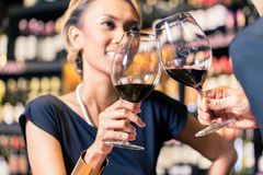 Asian couple drinking red wine. Close up of Asian couple toasting in wine shop Royalty Free Stock Photography