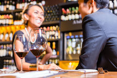 Asian couple drinking red wine. Asian Couple chatting in a wine shop Royalty Free Stock Images