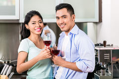 Asian couple drinking red wine in kitchen Stock Photos