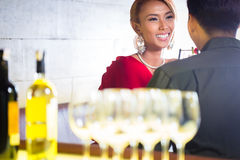 Asian couple drinking white wine in bar Stock Photo