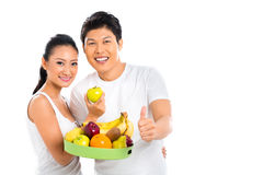 Asian couple eating healthy fruits Royalty Free Stock Photo