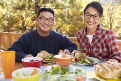 Asian couple eating outside at a table look to camera Royalty Free Stock Photos