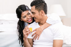 Asian couple embracing each other in bed Stock Photos