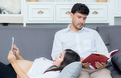 Asian couple family using a tablet at home, the young mother is pregnant on sofa. Stock Photo