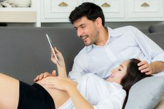 Asian couple family young mother and husband using a tablet. At home, women and men is pregnant lying on sofa looking tablet read book Stock Photos