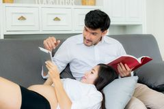 Asian couple family young mother and husband using a tablet. At home, women and men is pregnant lying on sofa looking tablet read book Royalty Free Stock Photography