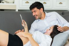 Asian couple family young mother and husband using a tablet. At home, women and men is pregnant lying on sofa looking tablet read book Royalty Free Stock Photo