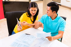 Asian couple fighting unpaid bills royalty free stock images