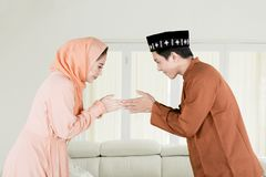 Asian couple forgiving each other at home. Asian couple forgiving each other by giving greets hand during Eid Mubarak celebration at home royalty free stock image