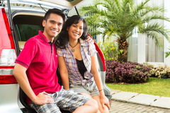 Asian couple is happy in front the car. And forwarding to a holiday Royalty Free Stock Photography