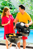 Asian couple having barbecue at the pool Stock Photography