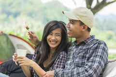 Asian couple having barbecue skewers. And coffee while camping Stock Photos